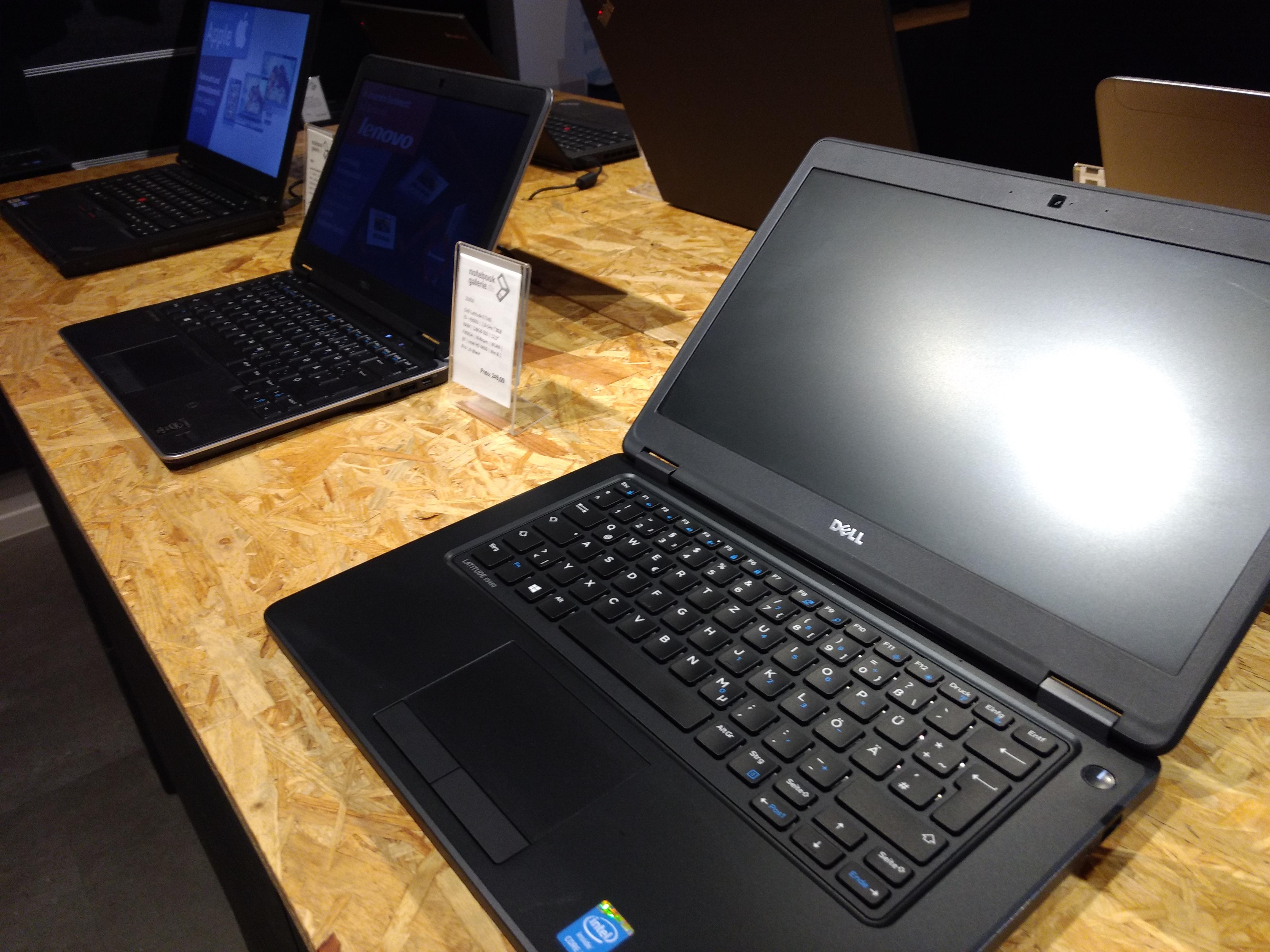 Blick auf einen Holztisch, auf welchem sich sechs aufgeklappte Laptops befinden.