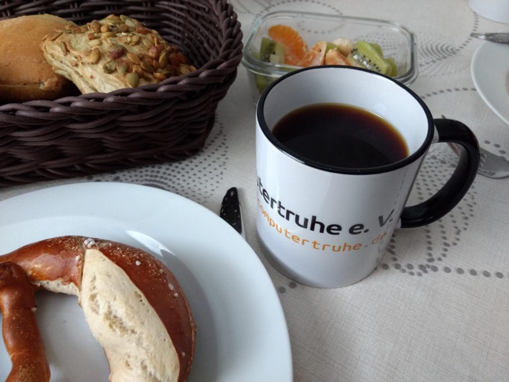 Eine mit Kaffee gefüllte Tasse mit dem Computertruhe-Schriftzug steht auf einem Frühstückstisch mit Gebäck und Obststückchen.