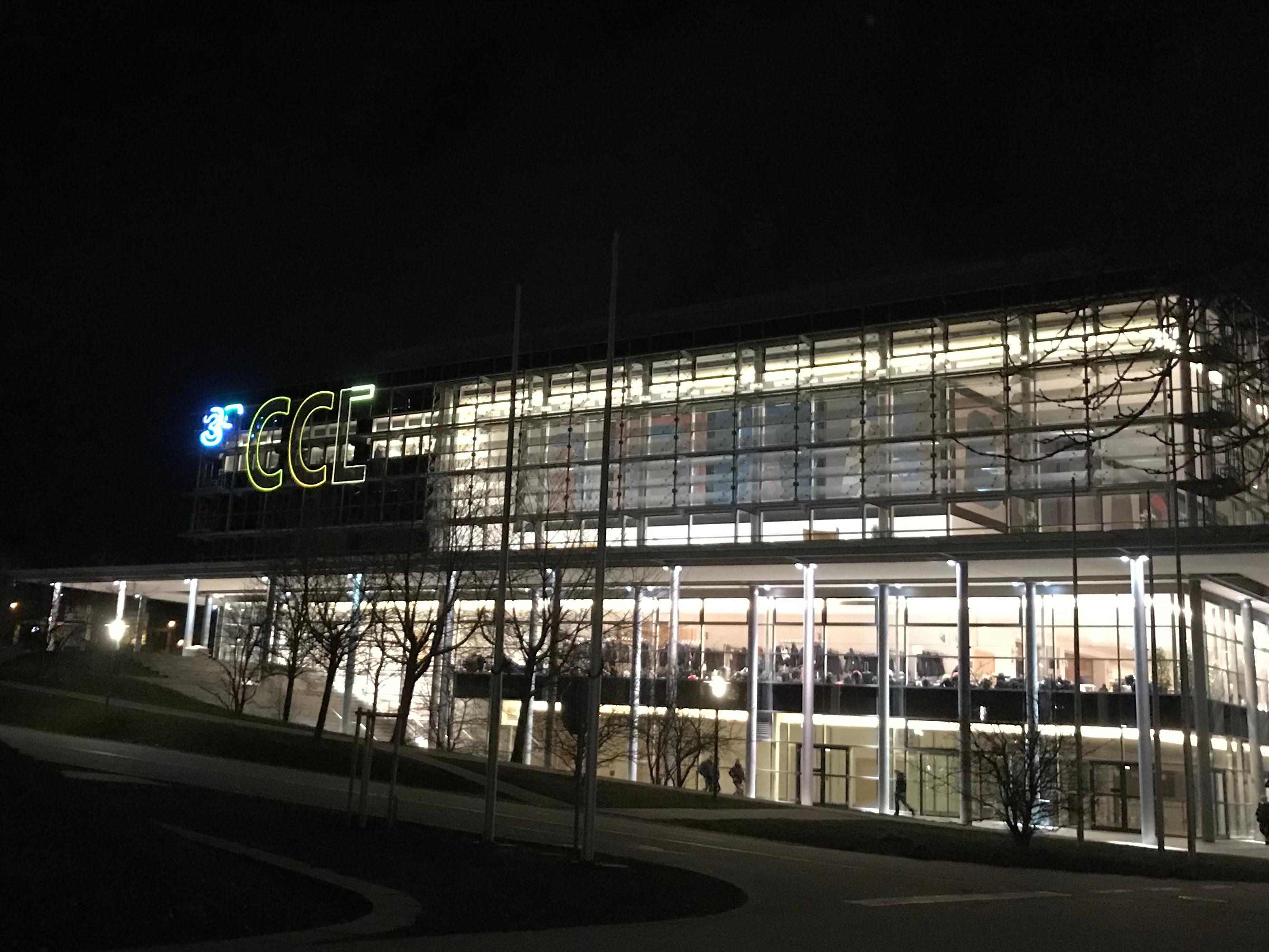 """Nächtlicher Blick auf einen Teil des Kongressgebäudes, bei dem die dort angebrachten Leuchtbuchstaben """"CCL"""" zu """"CCC"""" geändert wurden."""