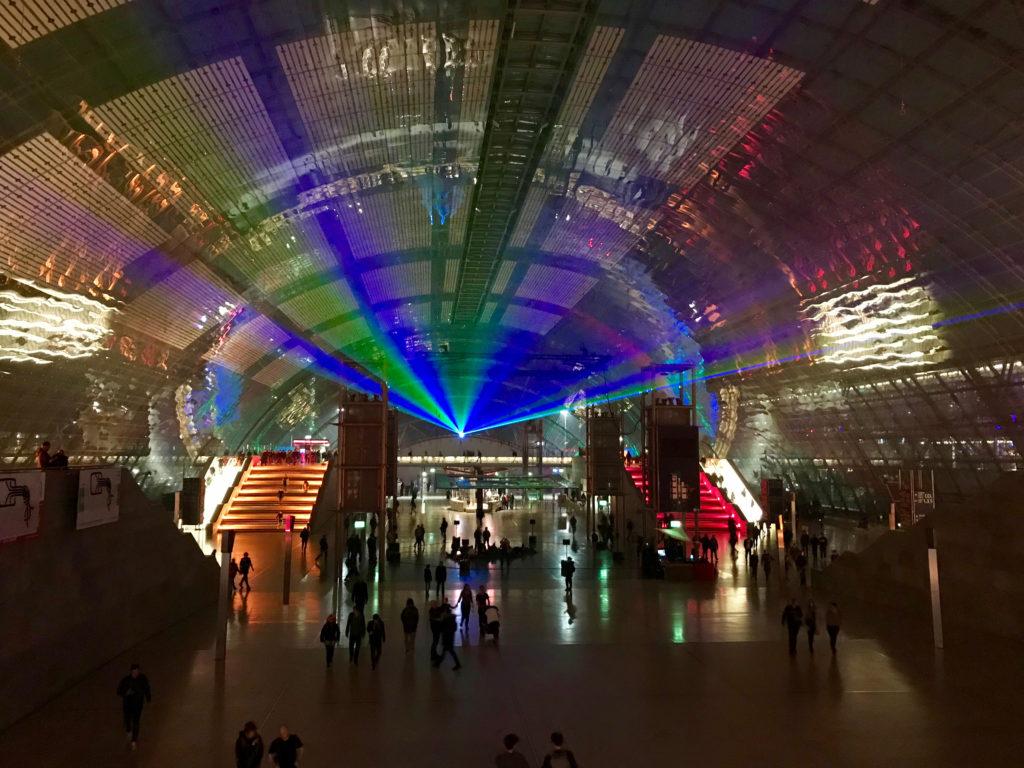 Ein Blick in die Eingangshalle des Kongressgebäudes. Es ist abends und ein Laserfächer befindet sich über den Menschen, die in der Halle umhergehen.