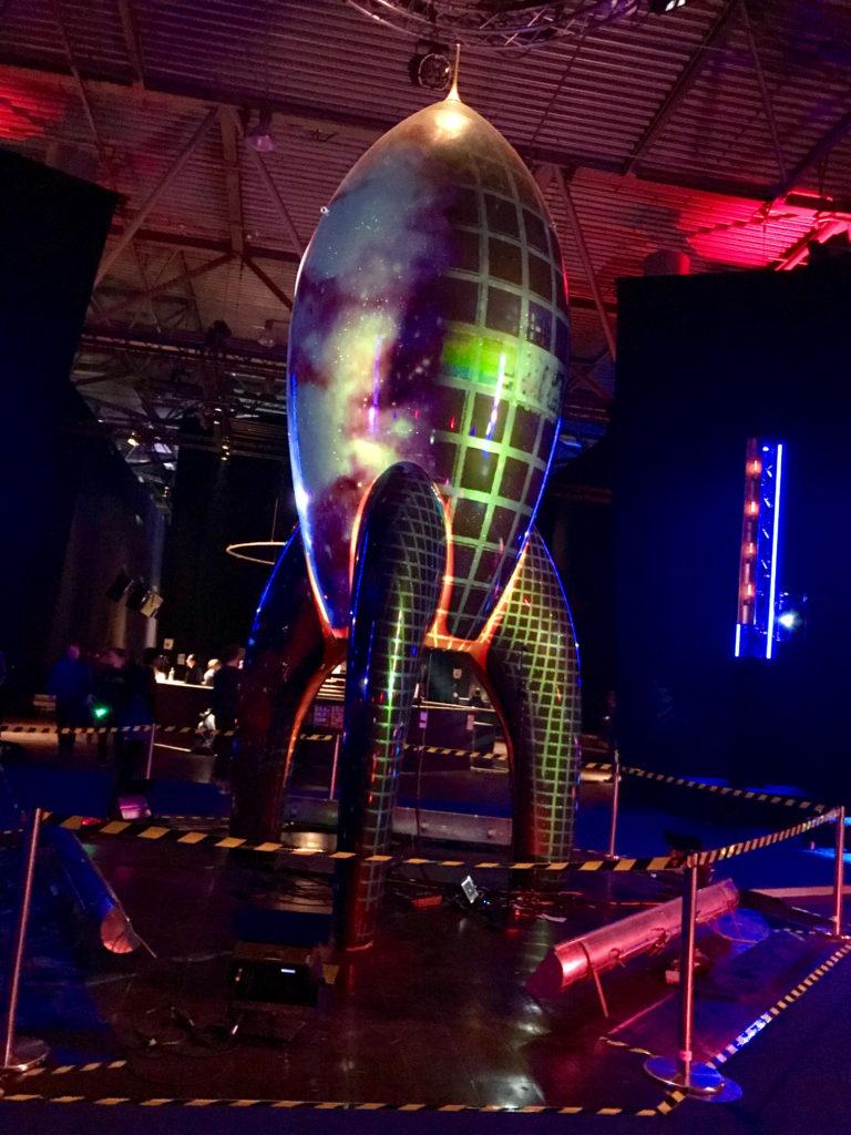 """Die große, grüne """"Fairydust""""-Rakete, eine Art Maskottchen des Clubs, steht inmitten einer dunklen Halle. Auf ihre Oberfläche werden diverse Animationen projiziert, u. a. die Nyan Cat."""
