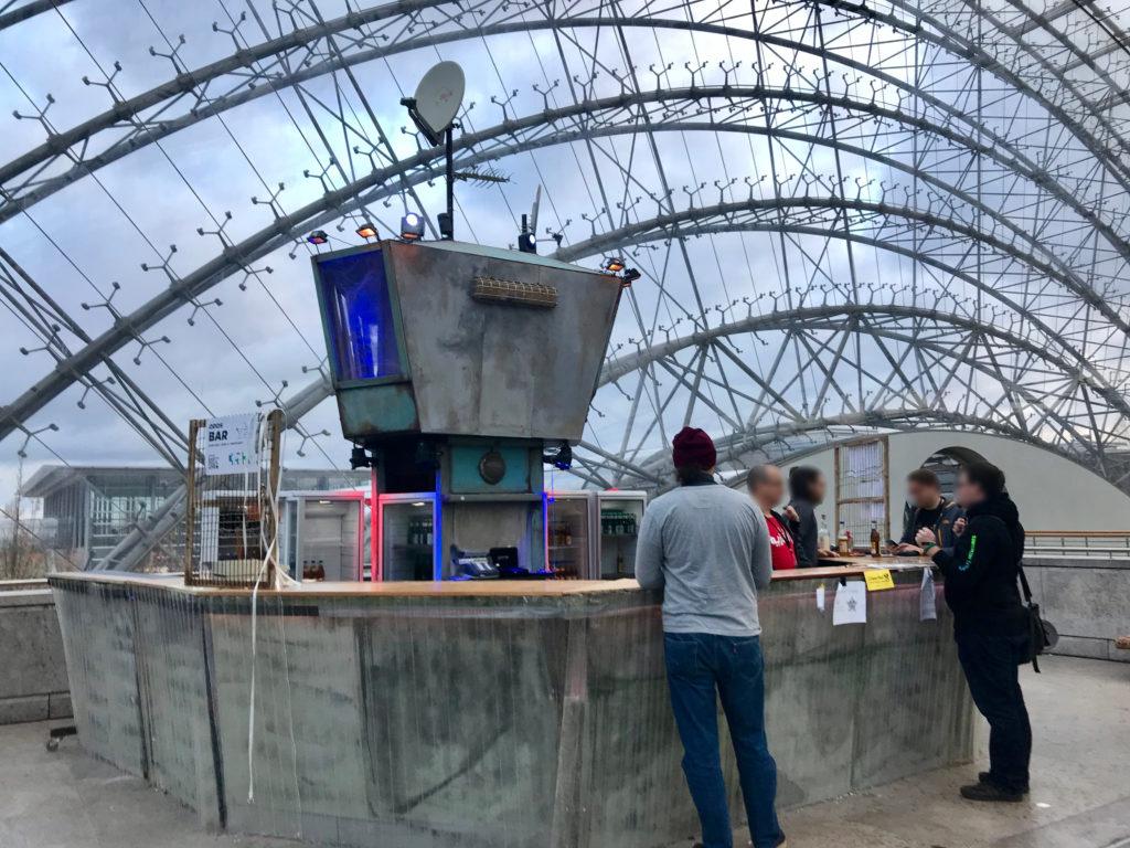 Eine futuristisch aussehende Bar mit mehreren Kühlschränken, die sich in der gläsernen Haupthalle befindet. Es ist Tag und man sieht den bewölkten Himmel hinter den Glaselementen des Daches. Zwei Personen stehen hinter und drei vor dem Tresen.