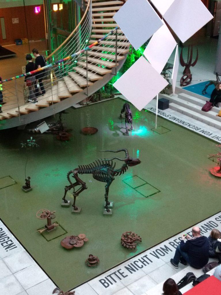 Wasserbecken mit Skulpturen aus Metall, die u. a. an Tierskelette oder Wasserpflanzen erinnern. Es sitzen vereinzelt Menschen um das Becken.