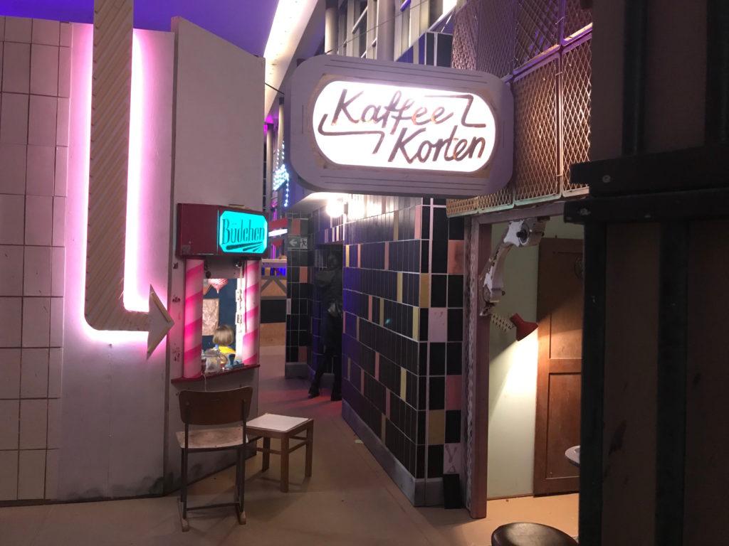 Eine Gasse der kleinen Stadt, in der sich ein Kiosk und gegenüber ein Café befinden. Und alles ist etwas kleiner als gewohnt.