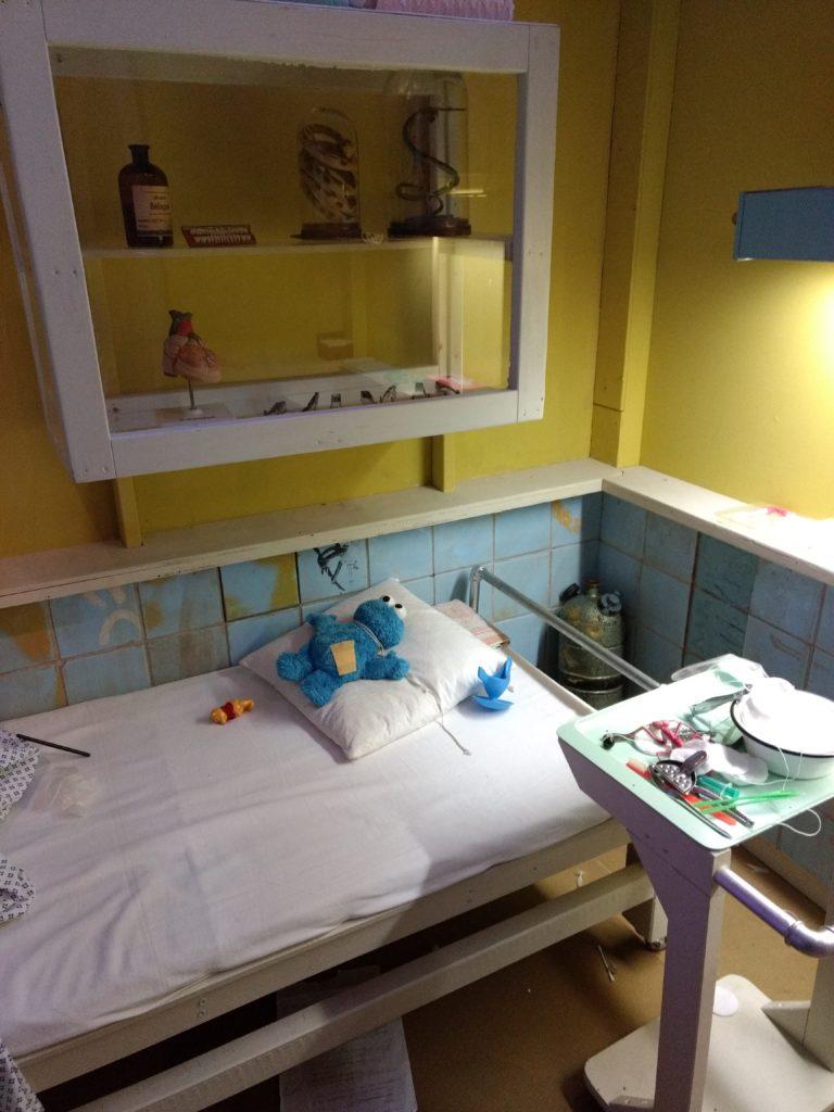 Krankenzimmer mit einem Bett, auf dessen Kopfkissen ein Krümelmonsterstofftier liegt. Daneben befindet sich auf einem Rolltisch diverses OP-Besteck (und eine Zitronenpresse 🤔). An der Wand über dem Bett hängt eine Glasvitrine, in der sich u. a. Schlangen in Glasbehältern, menschliche Zähne aufgereiht auf einem Brett und ein Modell eines menschlichen Herzens befinden.