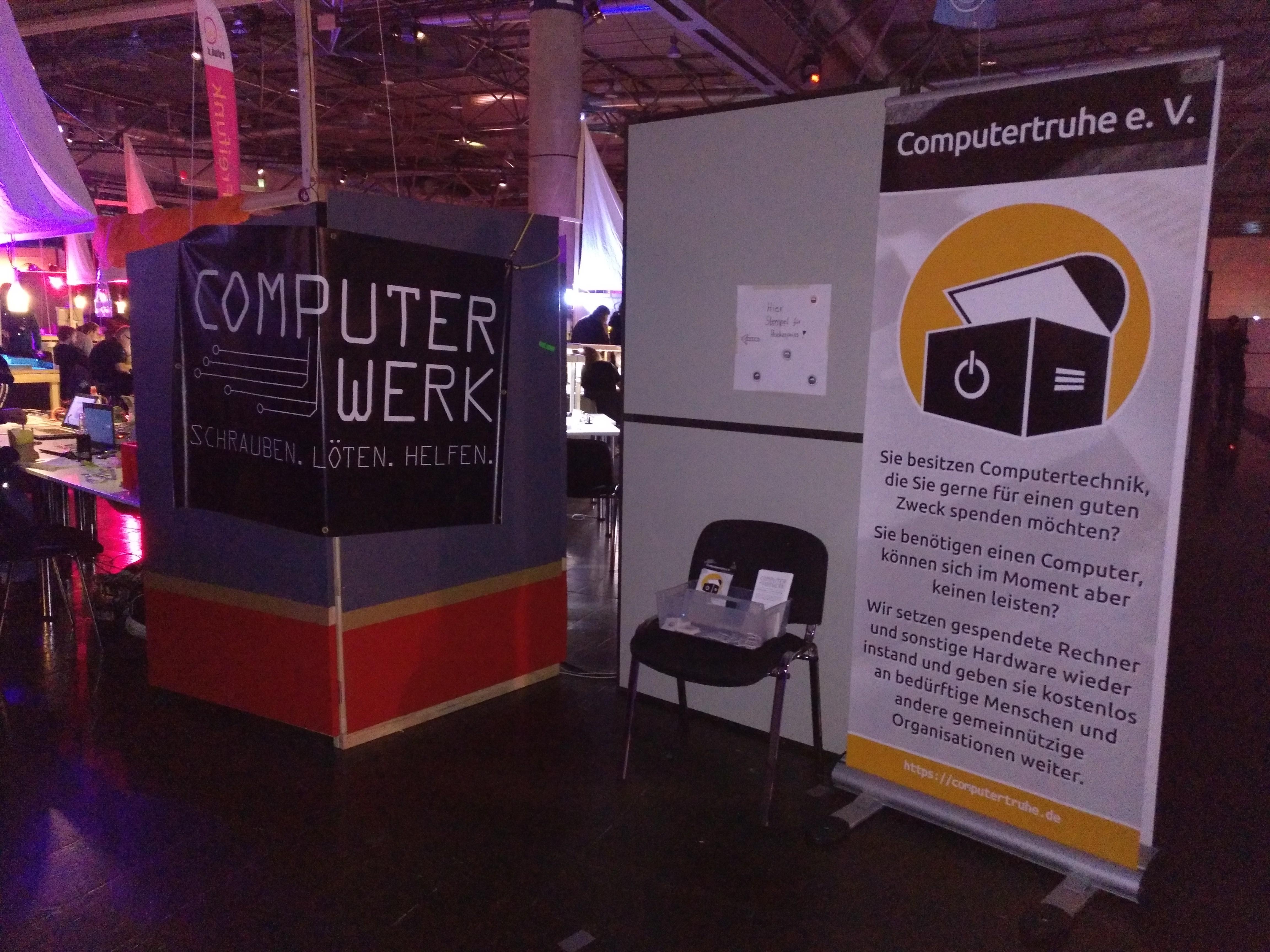 """Neben dem Roll-Up der """"Computertruhe"""" mit Logo und kurzem Infotext steht ein Stuhl mit Faltblättern und Werbeartikeln, wie Aufklebern und Pins. Außerdem hängt ein Banner mit dem Logo des """"Computerwerks"""" an einer Stellwand."""