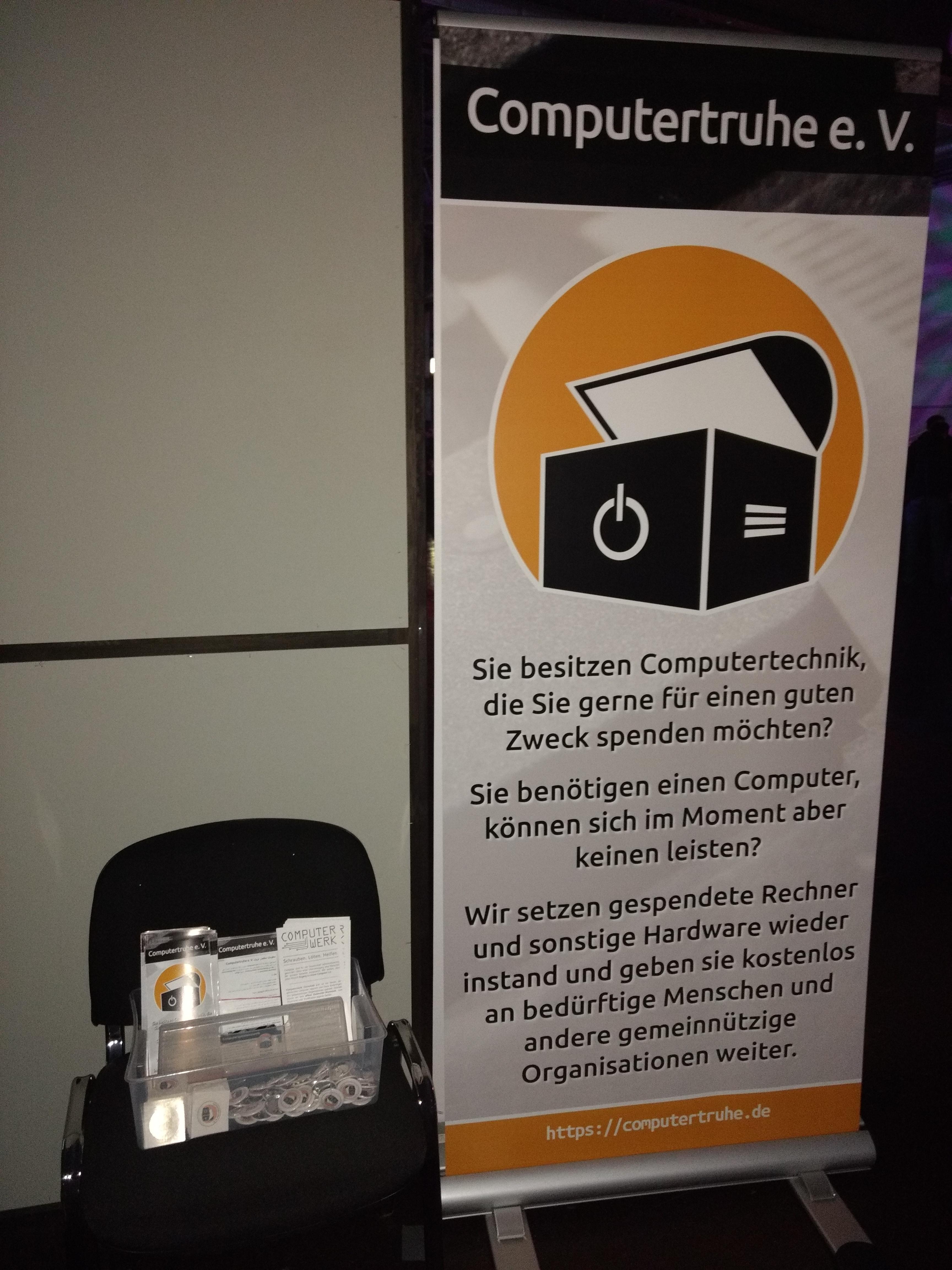 """Nahaufnahme des Roll-Ups der """"Computertruhe"""" mit Logo und kurzem Infotext und eines Stuhls, auf dem eine transparente Box mit Faltblättern und diversen Werbeartikeln steht."""