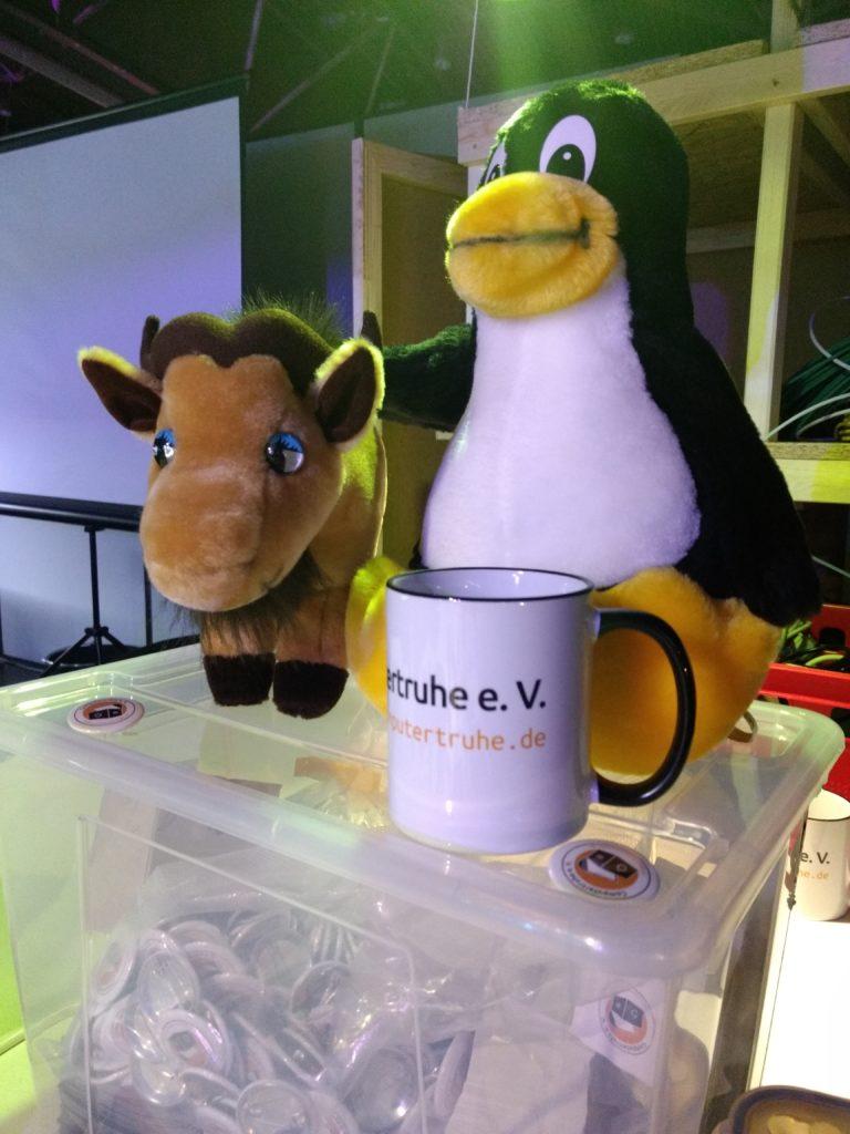 """Auf einer transparenten Box mit Werbeartikeln sitzen Plüschversionen des """"GNU""""- und des """"Linux""""-Maskottchens hinter eine Kaffeetasse mit dem """"Computertruhe""""-Logo."""
