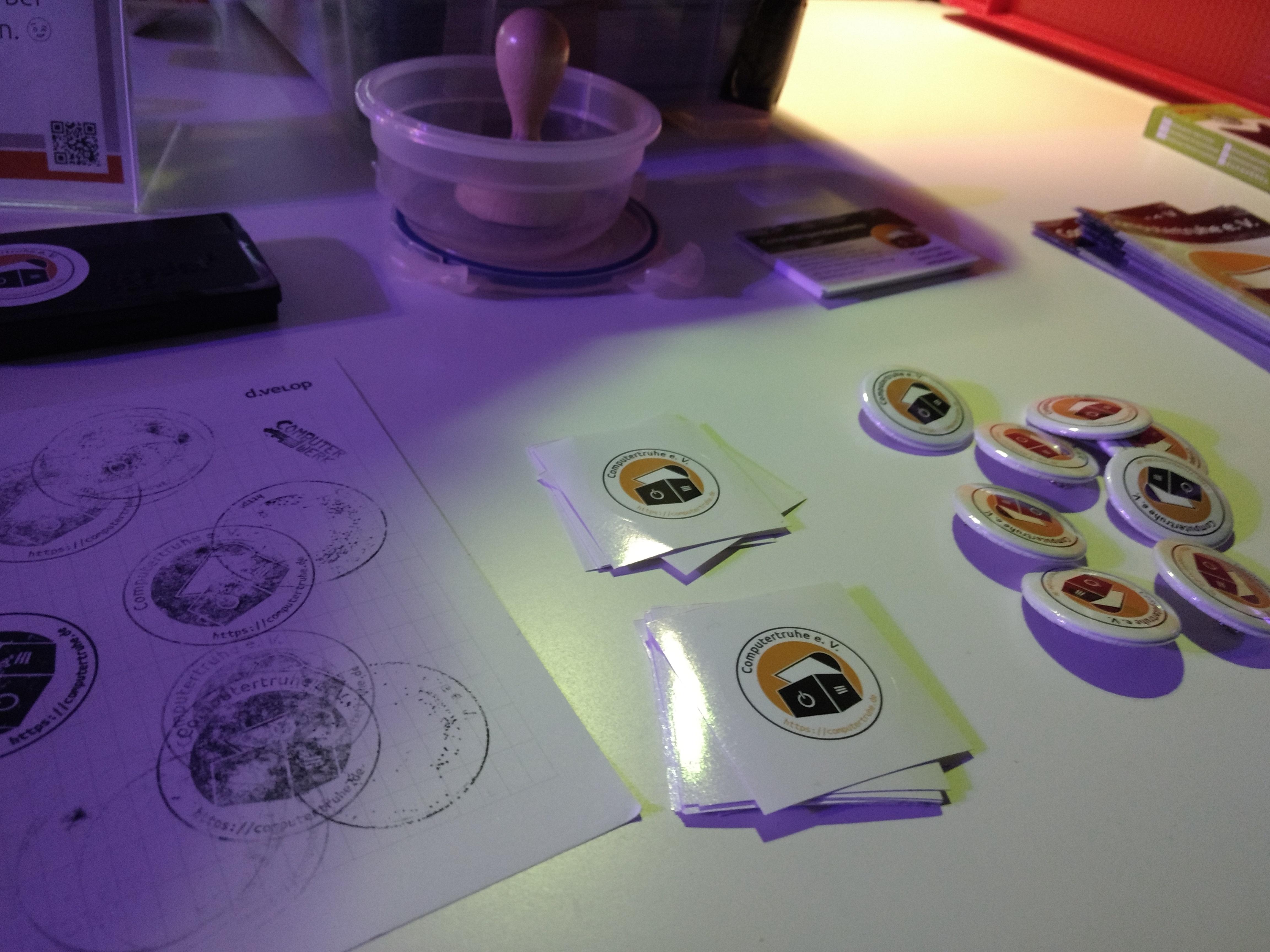 """Tischplatte, auf der Aufkleber und Pins mit dem """"Computertruhe""""-Logo darauf und Informationsmaterial drapiert sind. Ebenfalls ist ein Blatt Papier mit mehreren Abdrücken des Vereinsstempels zu sehen."""