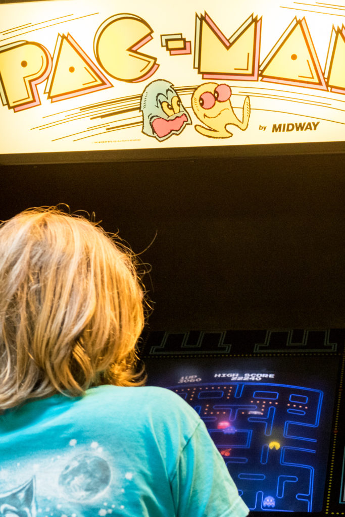"""Ein Kind sitzt vor einem Arcade-Automaten und spielt """"Pac-Man""""."""