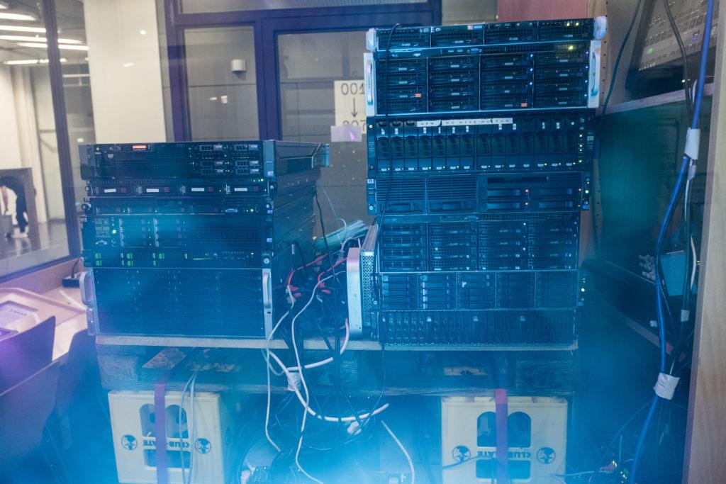 Frontansicht mehrerer übereinander gestapelter Server-Racks auf Europaletten und Matekisten.