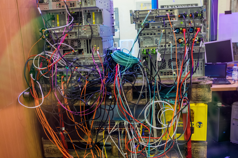 Rückansicht mehrerer übereinander gestapelter Server-Racks auf Europaletten und Matekisten, die mit vielen bunten Netzwerkkabeln verbunden sind.