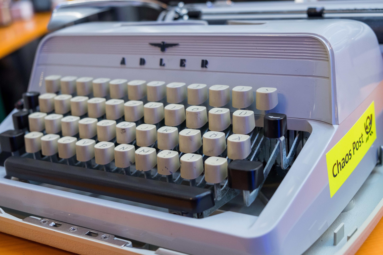 """Eine uralte """"Adler""""-Schreibmaschine mit einem """"Chaos Post""""-Aufkleber an der Seite."""