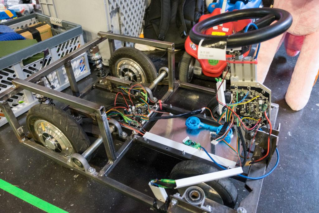 Vierrädriges, offenes Gefährt mit Lenkrad, bestehend aus einem Metallrahmen und diversen Elektronikkomponenten.