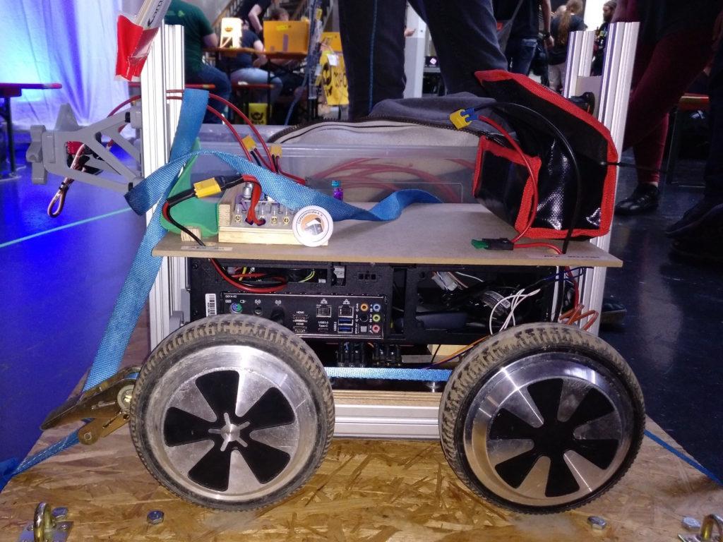 Seitenansicht eines vierrädrigen Roboters, in dessen Inneren die Rückseite eines herkömmlichen Computergehäuses erkennbar ist.