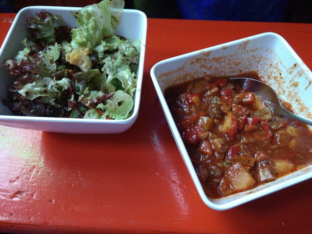 Eine Schale mit grünem Salat und eine Schale mit veganem Gulasch.