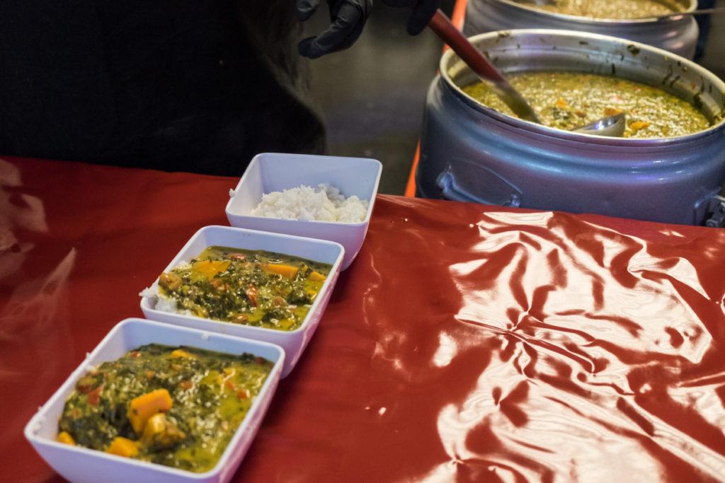 Im Vordergrund stehen zwei Schalen mit Curry, gefolgt von einer dritten, die nur Reis enthält. Im Hintergrund befindet sich ein großer Bottich voller Curry.