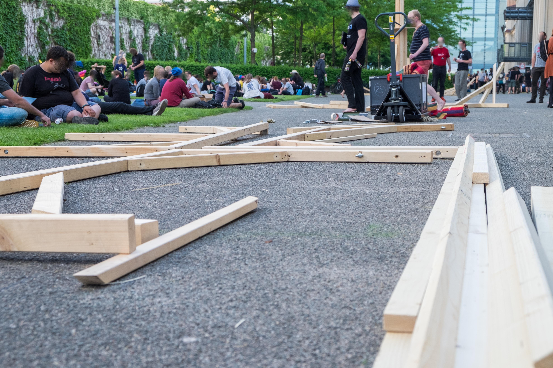 Auf dem asphaltierten Weg vor dem Gebäude liegen viele Holzlatten auf dem Boden. Auf der Wiese daneben befinden sich viele Menschen.