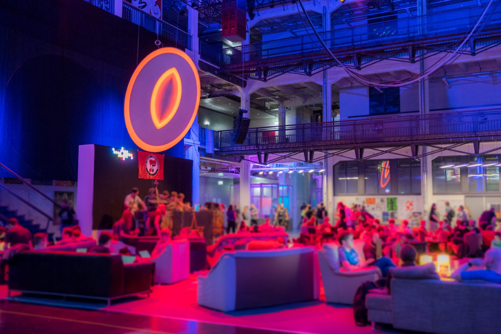 Die Lounge, bestehend aus vielen Sofas mit darin sitzenden Menschen, mit einer Bühne und einer runden Leinwand darüber. Alles ist in rotes Licht getaucht.