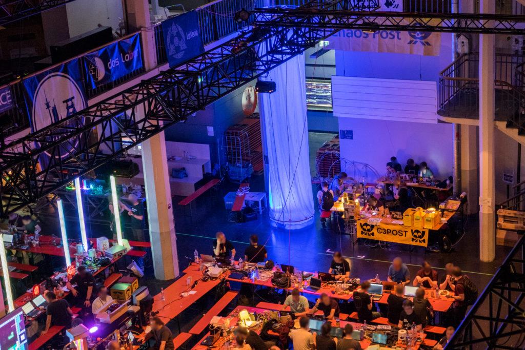 Blick auf das Hackcenter, das aus Biertischgarnituren besteht. An den Tischen sitzen Menschen, auf den Tischen befinden sich viele Laptops, Kabel und sonstige Technik.
