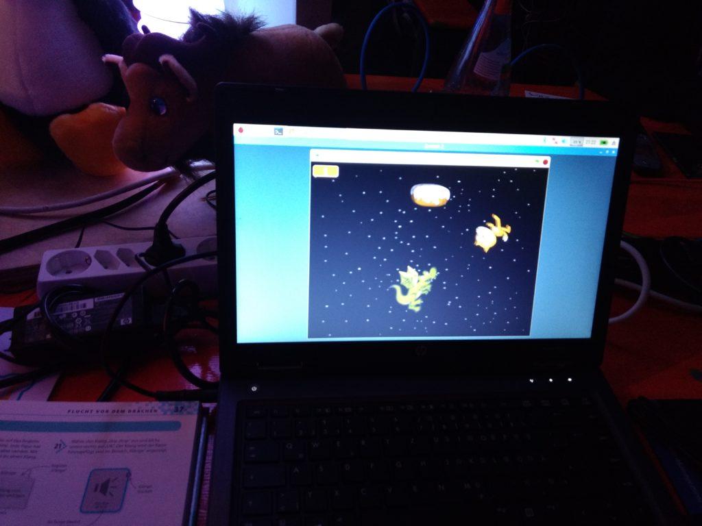"""Auf einem Laptop-Bildschirm sieht man ein laufendes """"Scratch""""-Programm. Im Weltall fliegen ein Drache, eine Katze und ein Donut."""