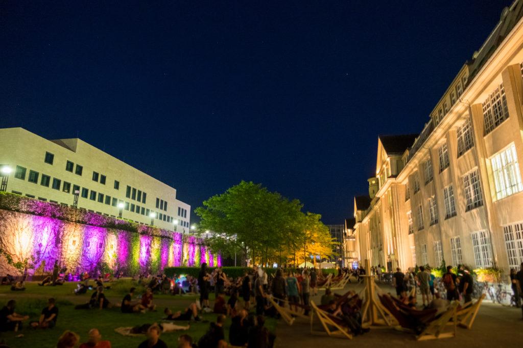 Blick auf den abendlichen Außenbereich. Leute tummeln sich auf dem Rasen oder liegen in Hängematten.