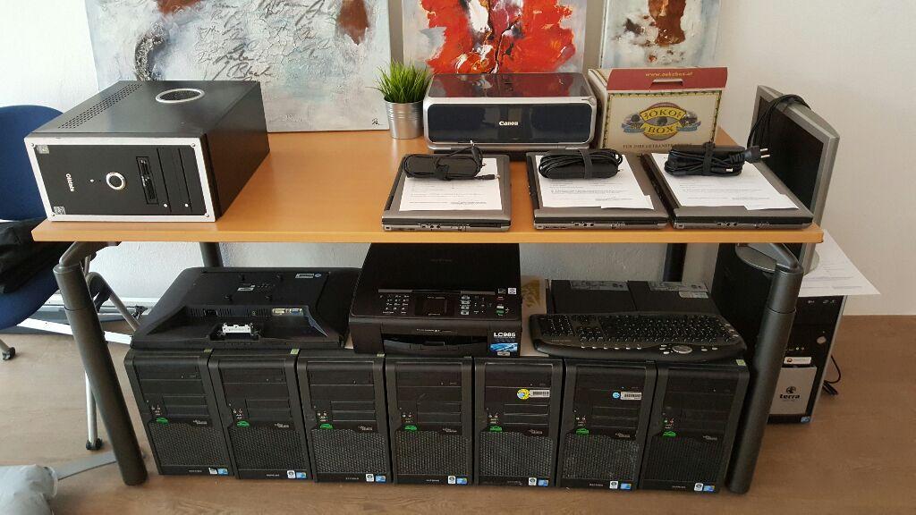 Tisch, auf und unter dem sich fein säuberlich platziert u. a. Desktops, Laptops und Drucker befinden.