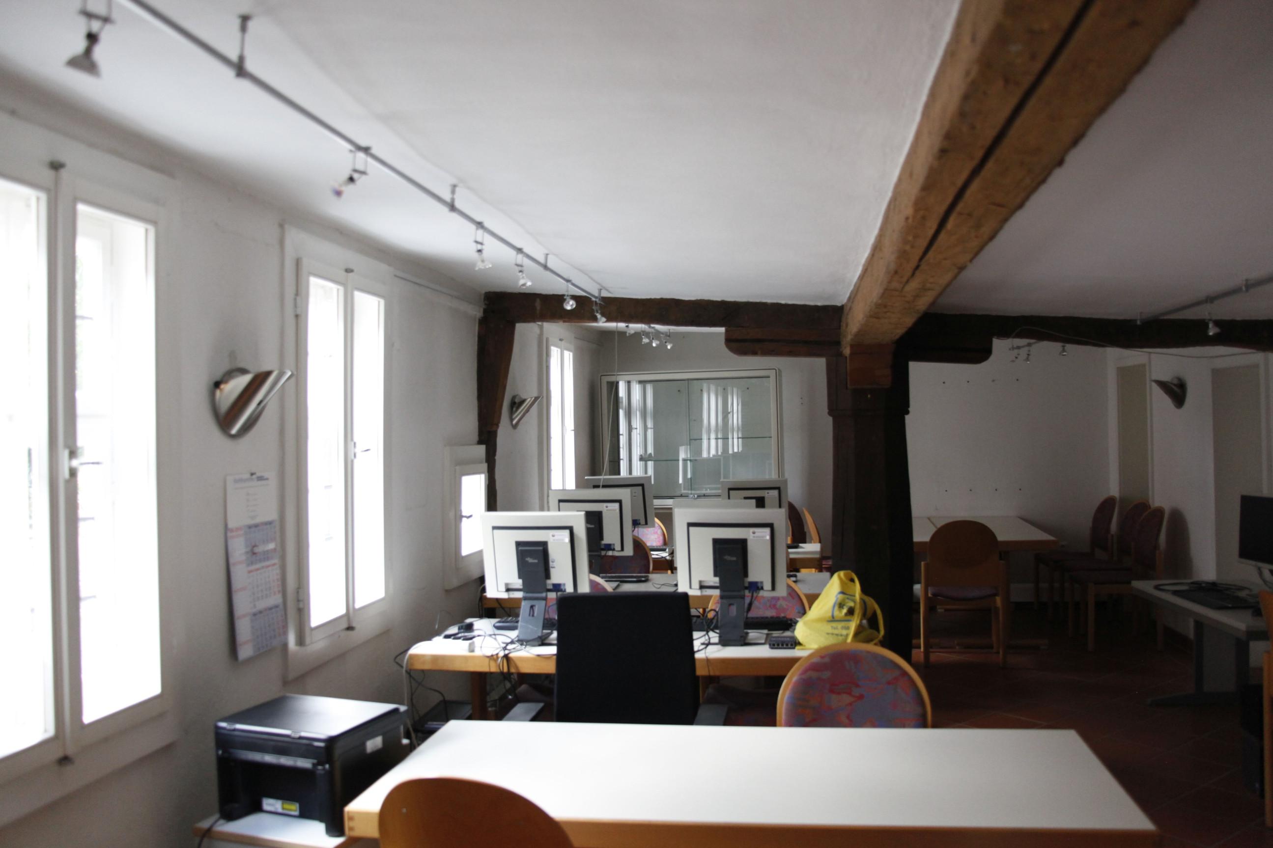 Blick auf sechs leere Computerarbeitsplätze, die sich in einem Raum mit dicken Holzbalken befinden.
