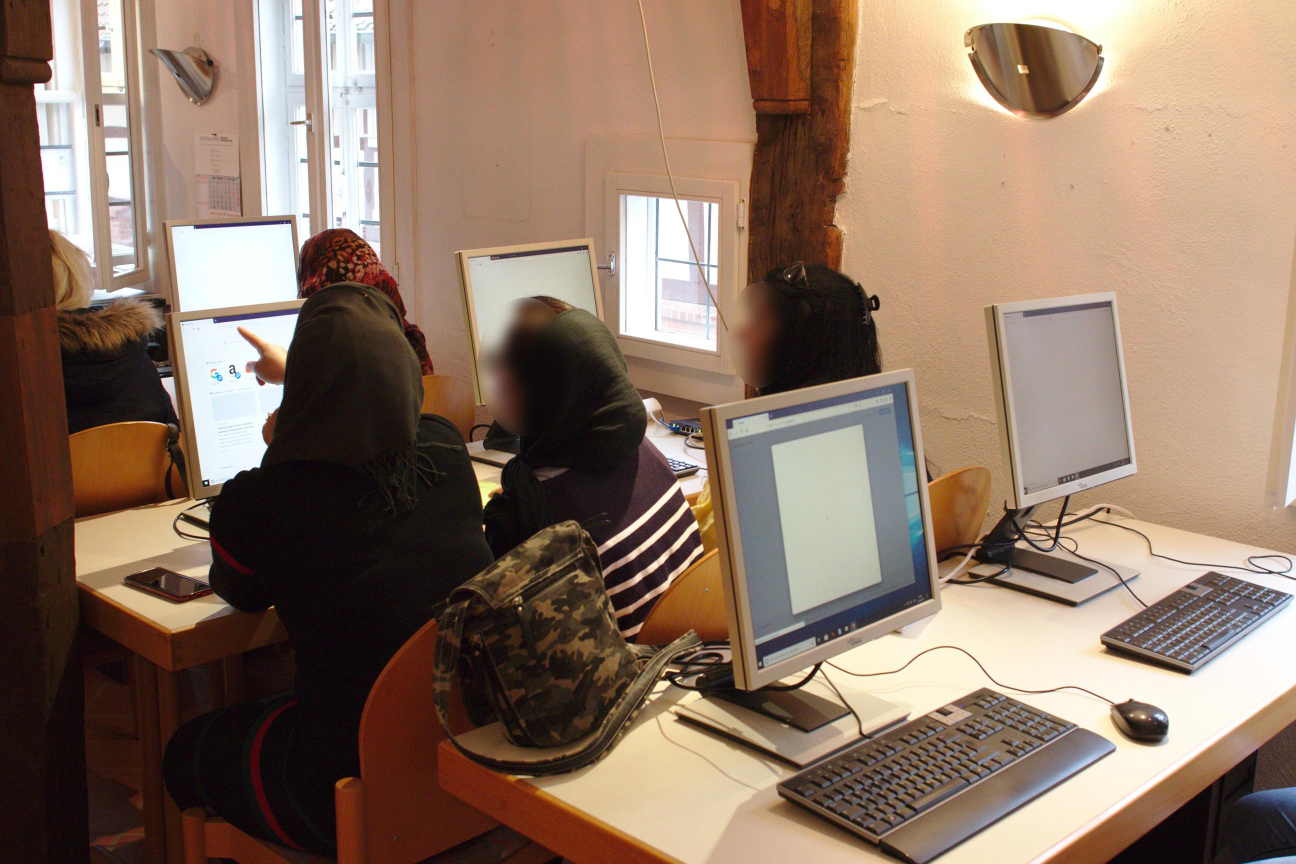 Fünf Frauen sitzen vor einigen Computern.