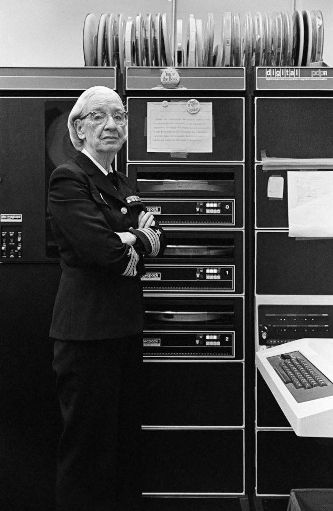 Grace Hopper in ihrer Navy-Uniform in ihrem Büro in Washington, D.C. Im Hintergrund sieht man eine PDP-11, im Vordergrund eine Tastatur.
