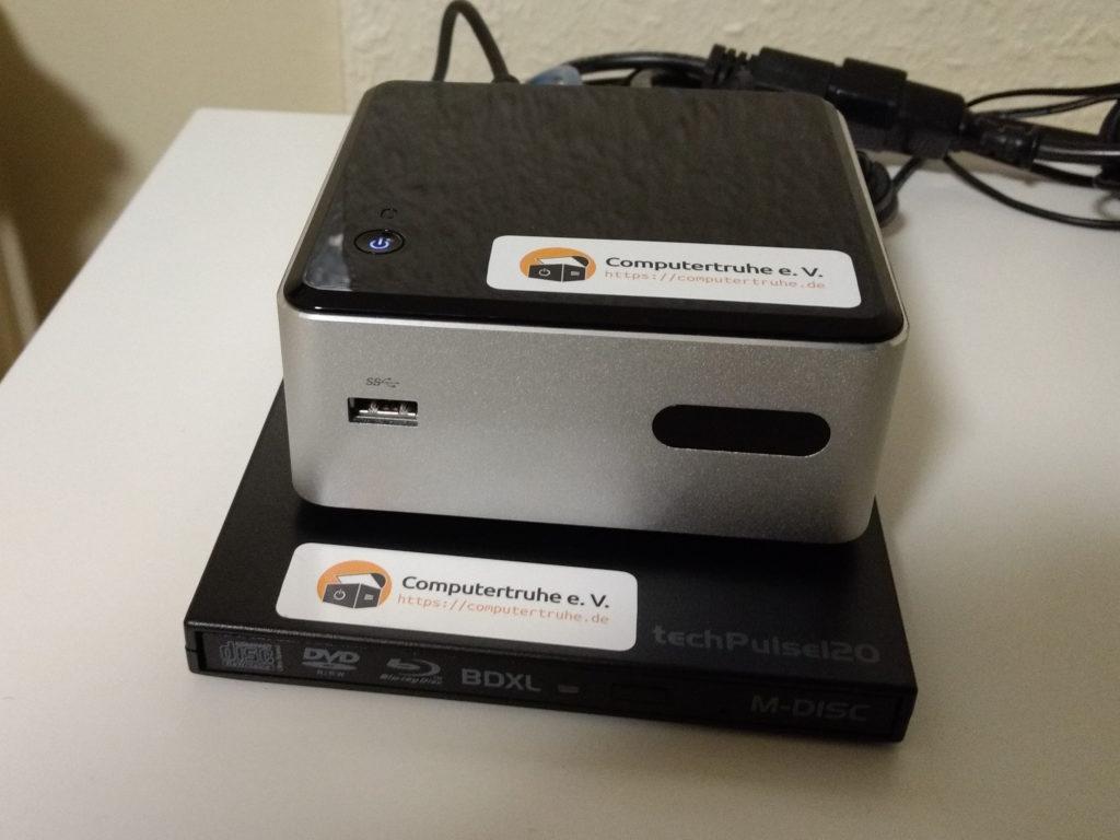 Intel NUC, der auf einem externen DVD-Laufwerk steht, das selbst mehr Standfläche als er Rechner belegt.