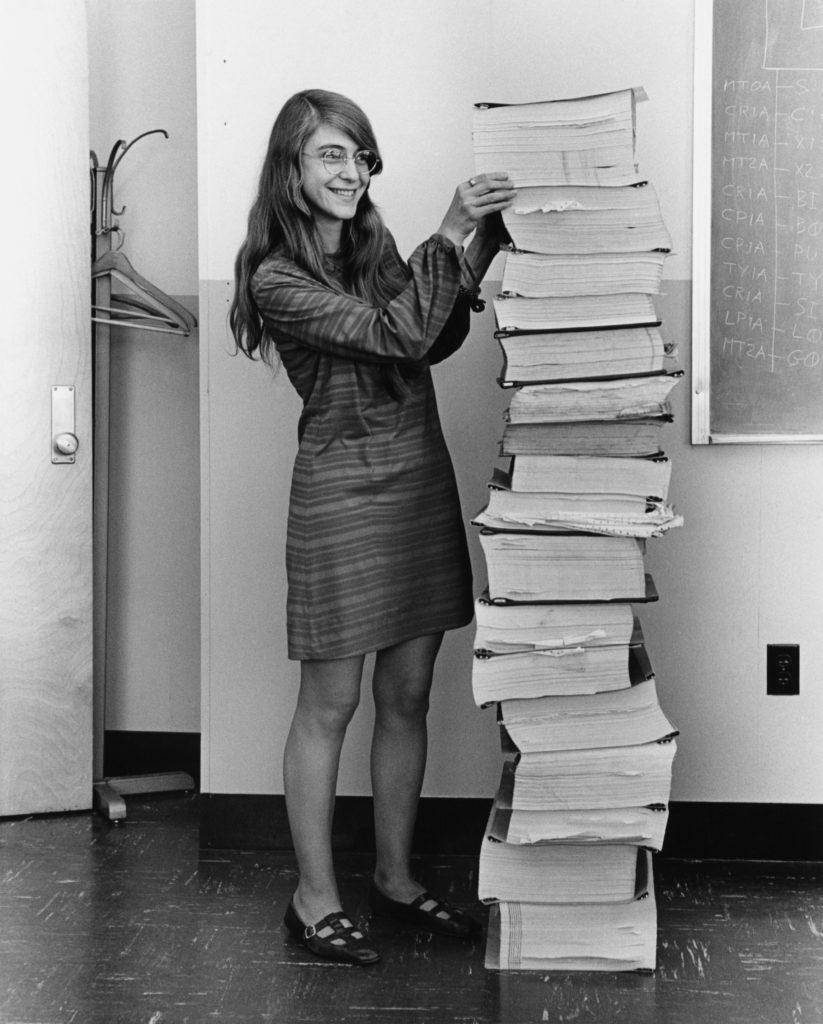 Margaret Hamilton steht neben einem Turm aus Papier, der genauso hoch wie sie groß ist.