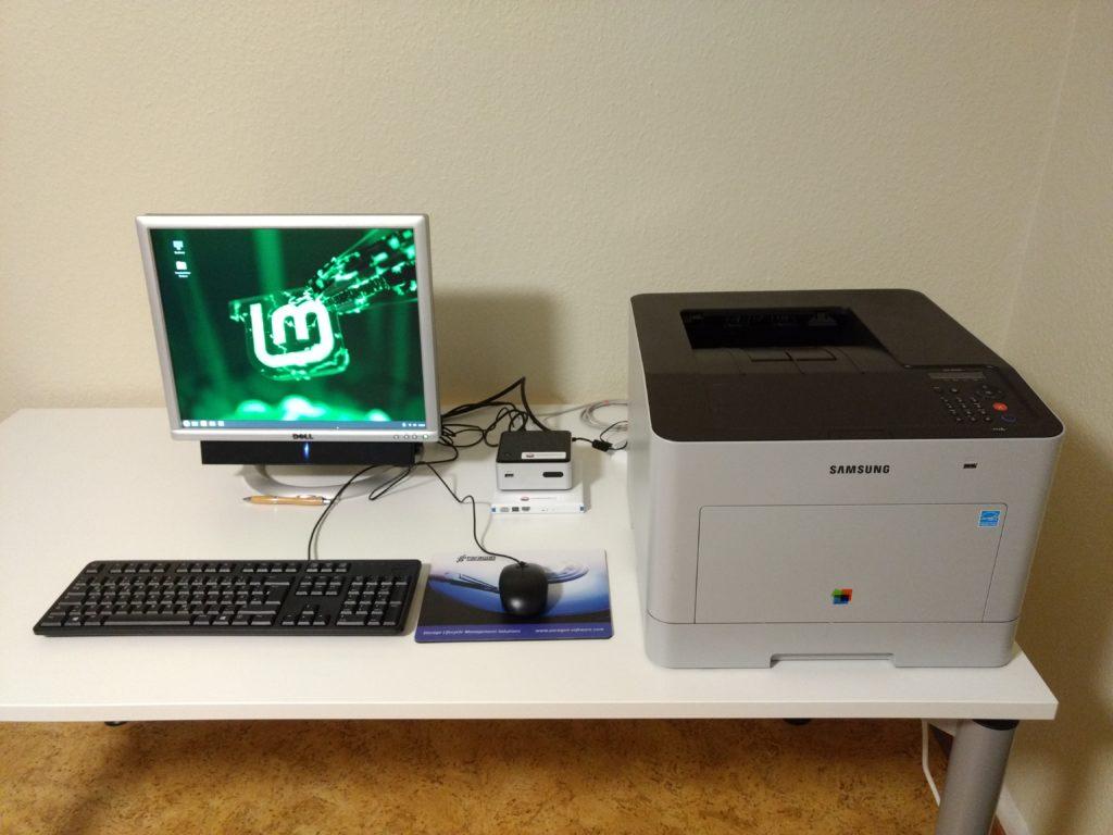 Tisch, auf dem sich ein Komplett-PC mit Eingaberäten und ein Laserdrucker befindet.