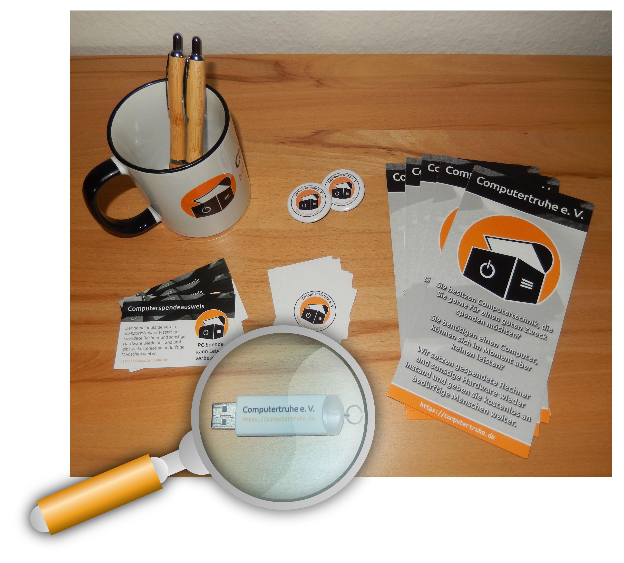 Auf einer Oberfläche aus Holz befinden sich Info- und Werbemittel des Vereins: Eine Tasse, zwei Kugelschreiber, zwei Ansteckpins, drei Computerspendeausweise, fünf Aufkleber, fünf Infofaltblätter und ein USB-Stick, der durch eine Lupe (bestehend aus einer Grafik) vergrößert dargestellt wird.