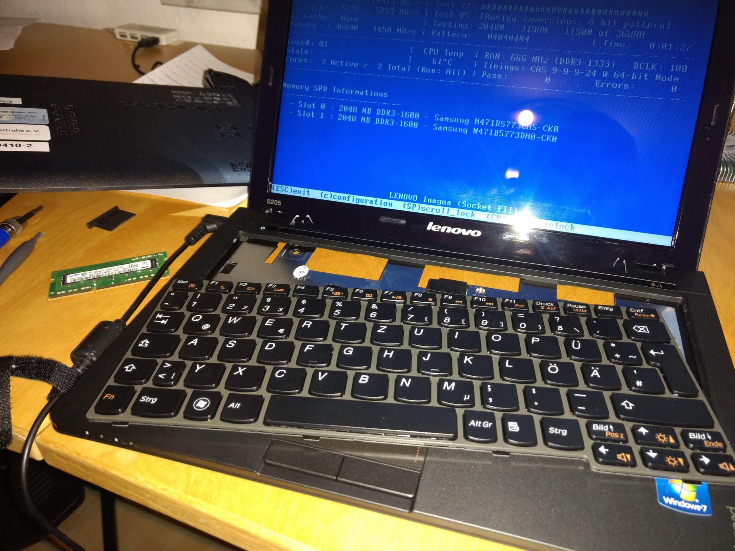 Auf einem Schreibtisch befindet sich ein laufendes Lenovo Ideapad S205, welches einen Speichertest durchführt. Die Tastatur wurde herausgelöst und neben dem Gerät liegt ein Speicherriegel, Werkzeug und die Bodenplatte des Laptops.