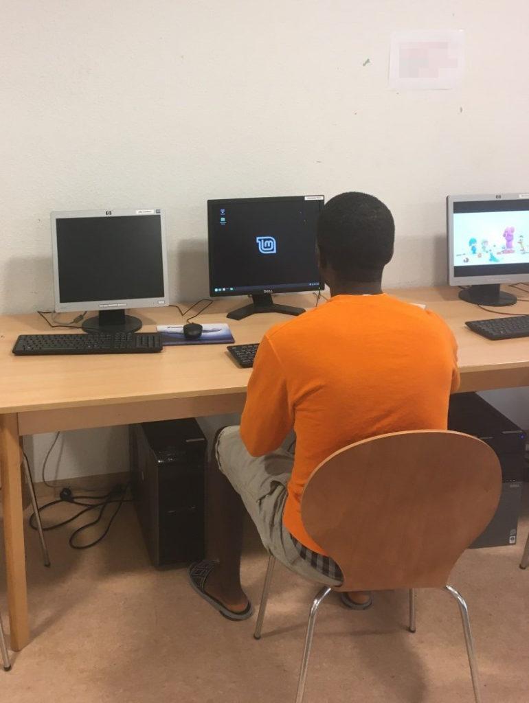 Auf Tischen, die parallel an einer Wand stehen, sieht man drei Monitore und Eingabegeräte. Darunter sind zwei Desktop-Gehäuse sichtbar. Ein Mann sitzt mit dem Rücken zur Kamera vor dem mittleren Bildschirm.
