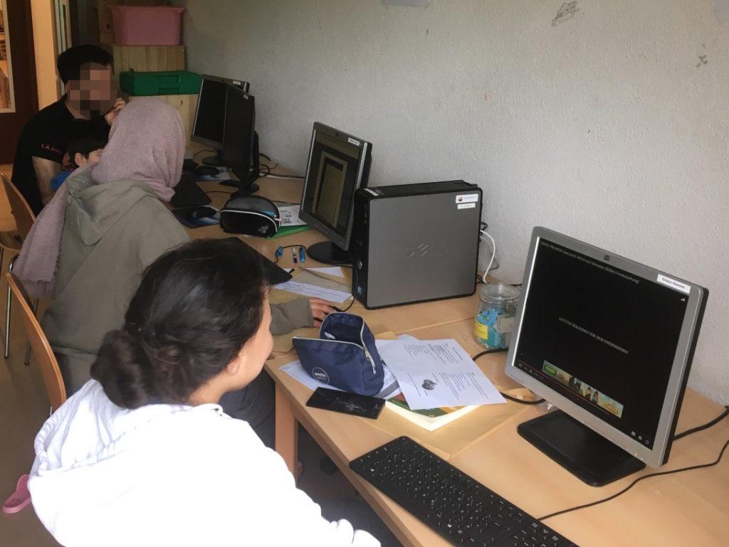 Auf Tischen, die parallel an einer Wand stehen, sieht man vier Monitore, einen kleinen Desktop-Rechner, Eingabegeräte, Schreibutensilien und vermutlich Aufgabenblätter. Zwei Frauen, ein Mann und ein Kind sitzen an den Tischen und nutzen zwei der Rechner.