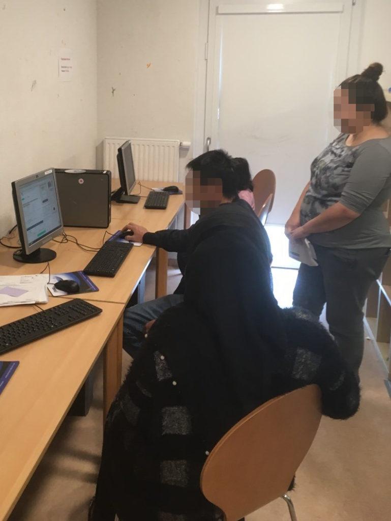 Auf zwei Tischen, die parallel an einer Wand stehen, sieht man zwei Monitore, einen kleinen Desktop-Rechner und je drei Tastaturen und Mäuse nebst Mauspads. Ein Mann nutzt einen der Rechner, während ihm zwei Frauen und ein kleines Kind zuschauen.