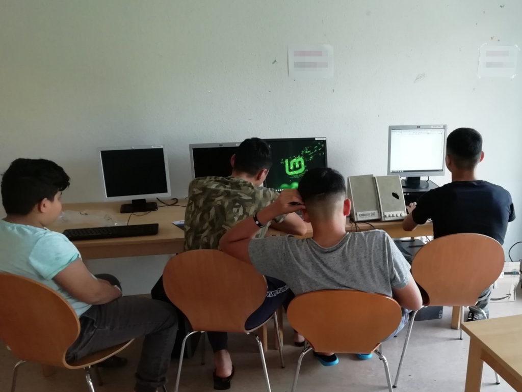 Auf zwei Tischen, die parallel an einer Wand stehen, befinden sich vier Monitore, von denen zwei eingeschaltet sind. Des Weiteren sieht man Eingabegeräte, Lautsprecherboxen und Desktop-Gehäuse. Davor sitzen vier Jugendliche mit dem Rücken zur Kamera.
