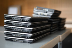 Auf zwei Tischen stehen drei unterschiedlich hohe Laptopstapel. Der vorderste Stapel besteht aus fünf baugleichen Geräten, die beiden hinteren sind unscharf.