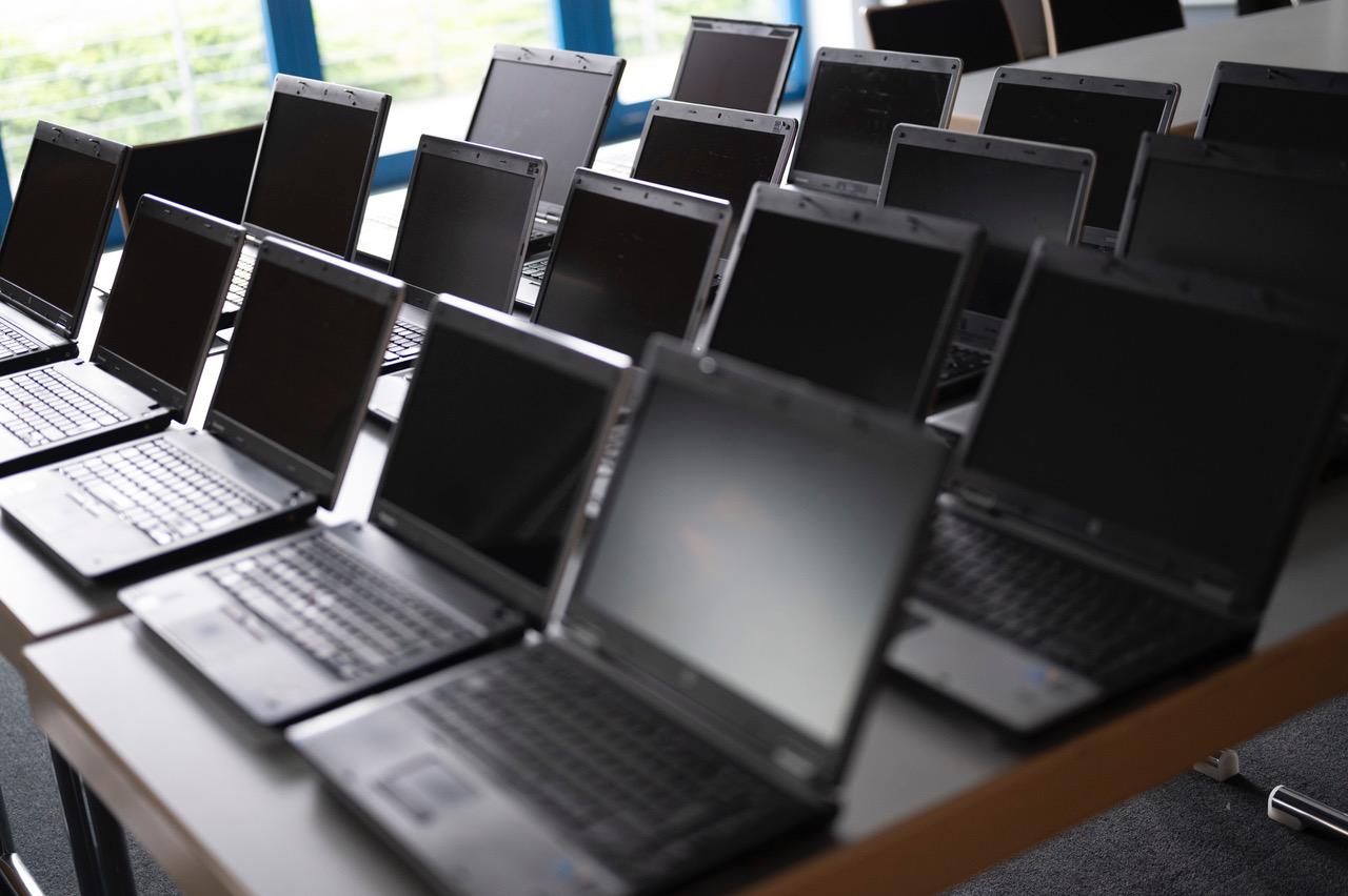 Auf mehreren Tischen verteilt sieht man 18 neben- und hintereinander angeordnete, aufgeklappte Laptops.