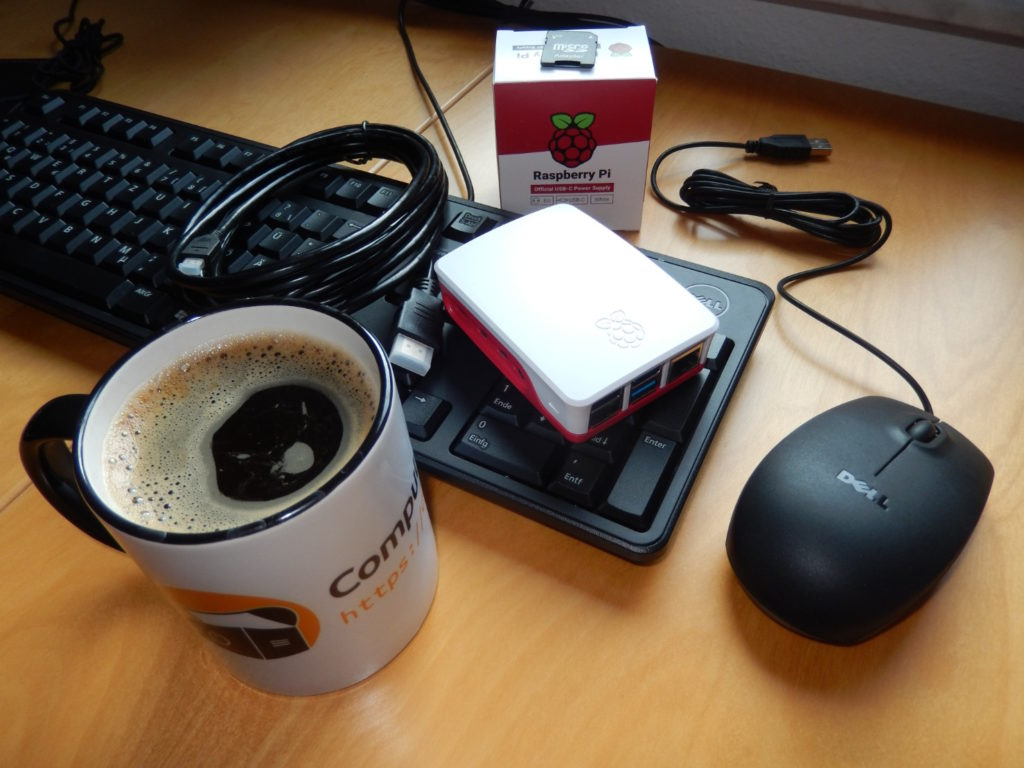 """Eine Tasse mit dem """"Computertruhe""""-Logo und -Schriftzug, die mit Kaffee gefüllt ist. Zusätzlich liegen auf dem Tisch eine Tastatur, Maus, ein HDMI-Kabel, ein verpacktes Netzteil und ein """"Raspberry Pi"""" in einem Gehäuse."""