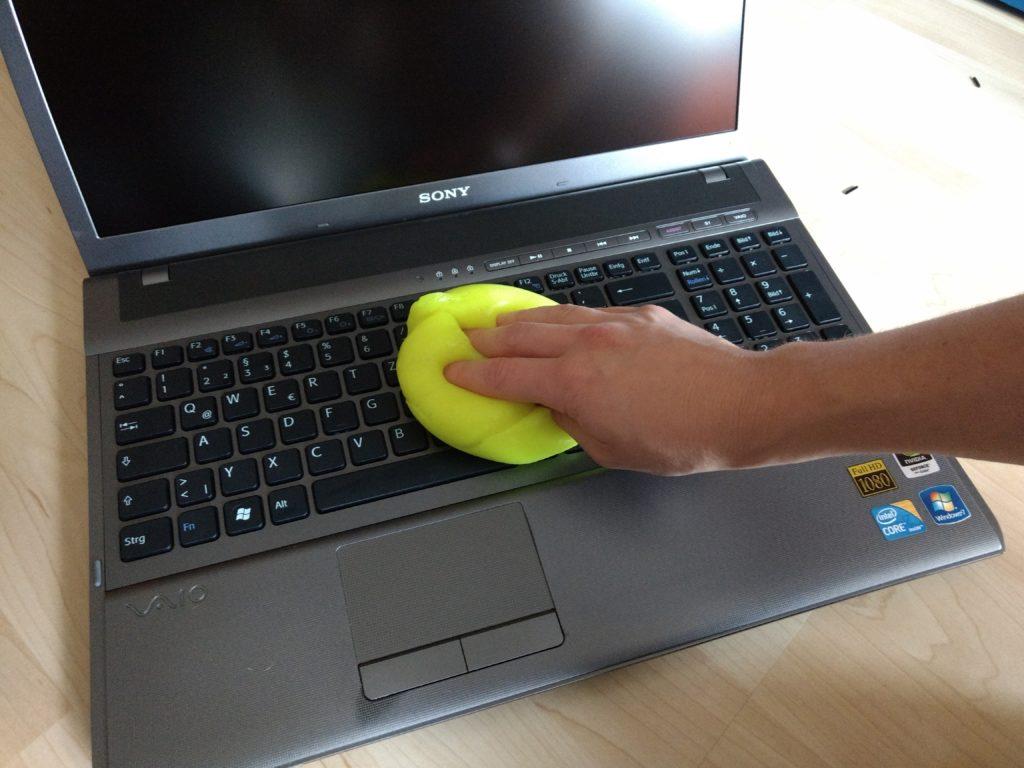 Die Tastatur eines SONY-Laptops wird mit einer gelben Reinigungsmasse gesäubert und desinfiziert.
