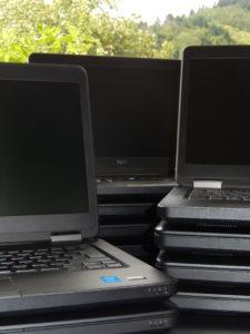 Auf einem Tisch im Freien befinden sich drei Laptopstapel. Zwei mit vier Geräten und einer mit zwei Geräten. Die obersten drei Computer sind aufgeklappt, aber ausgeschaltet.