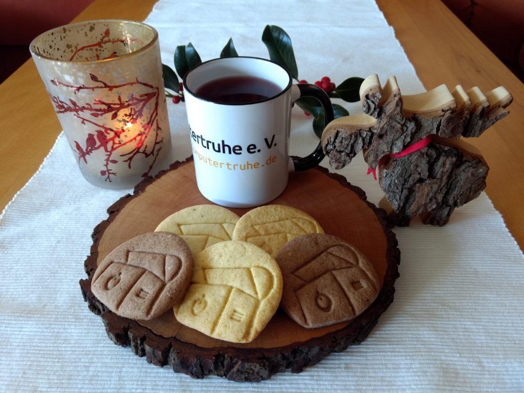 """Auf einem Tischläufer befindet sich eine Scheibe aus einem Baumstamm, auf der eine """"Computertruhe""""-Tasse mit rötlichem Tee und ein paar Keksen in der Form des Vereinslogos angeordnet sind. Dahinter liegt ein Zweig einer Stechpalme, links steht ein Windlicht mit brennender Kerze darin, rechts befindet sich ein aus einem Baumrindenstück ausgesägter Elch."""