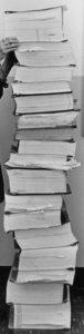 Ein Schwarzweißfoto zeigt einen hohen Stapel bestehend aus dicken Ordnern. Der Stapel wird ganz oben von zwei Händen gehalten.