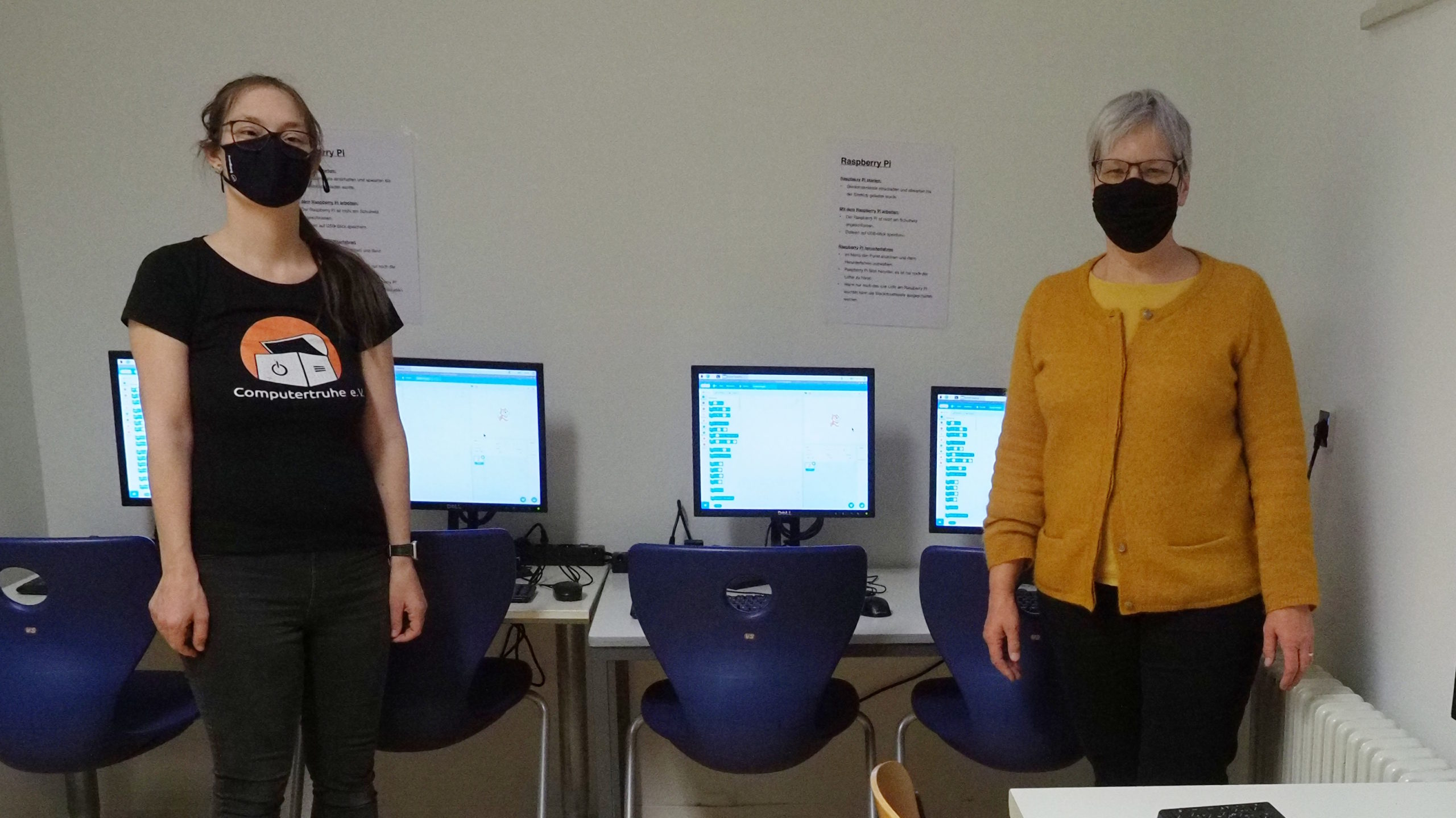 """Julia Fiedler und Heidrun Albert stehen mit Abstand und Mund-Nasen-Schutzmasken im neuen Computertraum. Hinter ihnen befinden sich auf zwei Tischen verteilt vier Computerarbeitsplätze. Auf den eingeschalteten Monitoren lassen sich """"Scratch""""-Programme erahnen."""