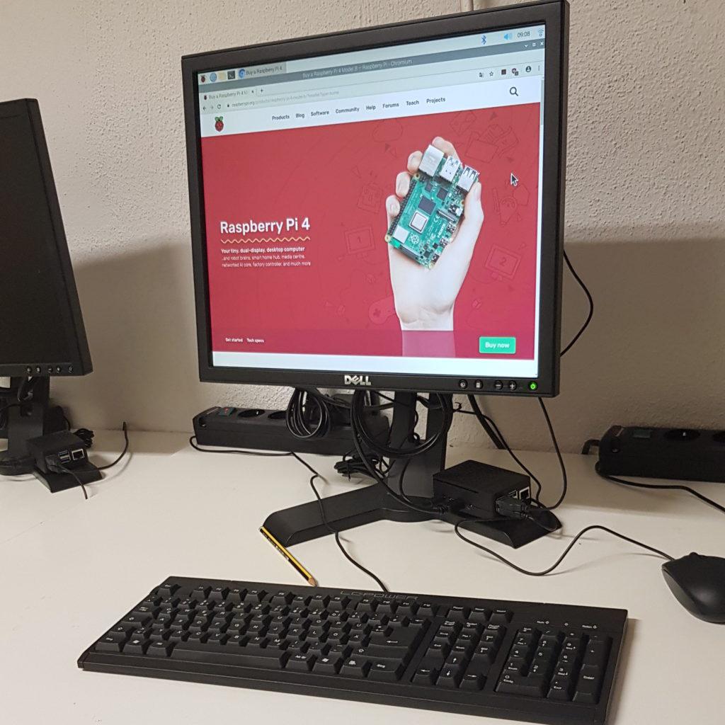 """Ein Rechnerarbeitsplatz bestehend aus einem Bildschirm, auf dessen Standfuss ein """"Raspberry Pi"""" in einem Gehäuse befestigt ist, einer Tastatur und einer Maus. Der Bildschirm zeigt eine Website des """"Raspberry Pi""""-Projekts an, die das neueste Modell, den """"Raspberry Pi 4"""", anpreist. Im Hintergrund befinden sich zwei Steckdosenleisten."""