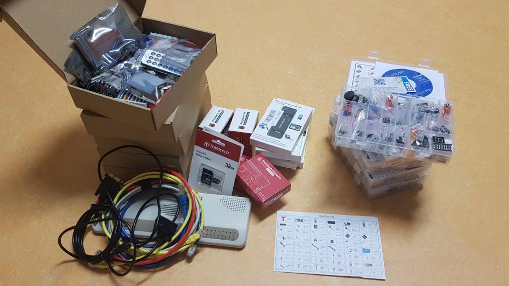Es sind diverse Schachteln und Sortierboxen zu erkennen, in denen sich elektronische Bauteile und Kabel befinden. Zudem sieht man weiteres Zubehör und Netzwerkkomponenten.